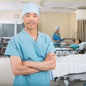 Portrait of confident mid adult male nurse standing in hospital ward