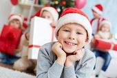 Image of cute lad in Santa cap looking at camera with company of friends behind
