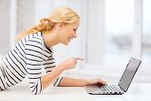 education and internet concept - smiling student girl pointing her finger at laptop screen in college