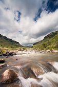 River Landscape In Drakensberg With Dramatic Clouds