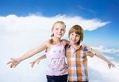 Fliers. Kids play and have fun together. Children playing fly over blue sky with clouds