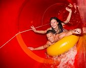Couple In Water Slide At Public Swimming Pool