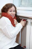 Smiling Woman Turning Thermostat On Central Heating Radiator