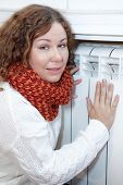 Frozen Woman Leaning To Central Heating Convector For Warming Hands
