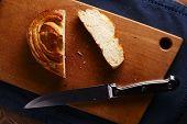 Sliced Bun On A Breadboard With A Knife