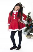 Little Girl In Santa Claus Costume And Reindeer Antlers