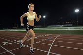 Woman running on a track at night