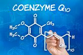 Hand with pen drawing the chemical formula of coenzyme Q10