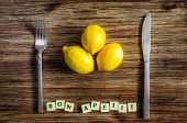 Silverware And Lemons On Wooden Table With Bon Apetit Sign