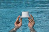 hands above water holding cup of coffee- relax in water