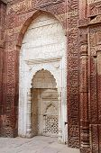 White mihrab in Qutub mosque ruins in Delhi (India) decorated with islamic sentences from Koran