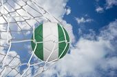 Football in nigeria colours at back of net against bright blue sky with clouds