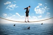 Businesswoman performing a balancing act over shark infested sea under blue sky