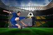 Composite image of football player kicking ball through tv against large football stadium with brasilian fans