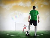 Composite image of football player about to take a penalty against football pitch under yellow sky