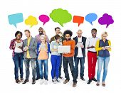 Group Of Multi-Ethnic Group Of People Holding Electronic Devices To Social Network And Colorful Speech Bubbles Above