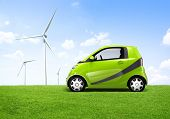 Electric green car in the outdoor with a view of windmill behind it.