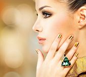 stock photo of emerald  - Glamour woman with beautiful golden nails and emerald ring on hands - JPG