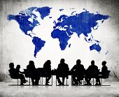 Business People Discussing Around The Conference Table And A Blue Cartography Of The World Above.