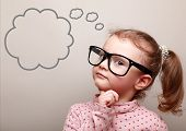 stock photo of cute  - Cute thinking kid girl in glasses with empty bubble looking - JPG