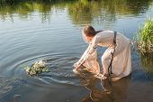 Beautiful girl lowers wreath in water