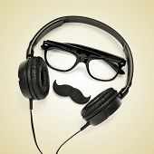 a pair of glasses, a mustache and a pair of headphones on a beige background, depicting a hipster gu