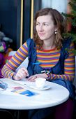 Beautiful Girl In Bright Clothes Writing Postcards In Cafe