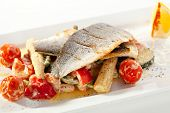 Fillet of Seabass with Tomato and Mussels Sauce. Garnished with Vegetables