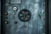 Grunge style image of old metal door background with vault lock.