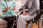 stock photo of hospice  - Nurse talking with disabled patient at home - JPG
