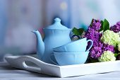 Composition with tea set and bouquet of beautiful spring flowers on tray, on wooden table, on bright