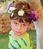 Very beautiful little boy posing in the garden. This holiday - his birthday. He wore a wreath of flowers