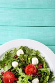 Green salad made with  arugula, tomatoes, cheese mozzarella balls and sesame  on plate, on color woo