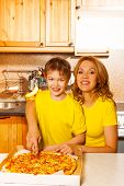 Boy and mother looking forward slicing pizza