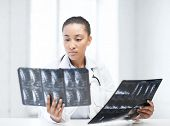 healthcare, medical and radiology concept - african doctor looking at x-rays