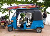 WELIGAMA, SRI LANKA - MARCH 7, 2014: Blue tuk tuk vehicle transporting surfboards on the roof. Touri
