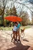 Lovely Young Couple Standing And Hugging Near The Bicycle With Red Dirigible In The Park