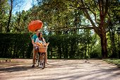 Lovely Young Couple Riding Bicycle With Red Dirigible And The Basket Full Of Baguettes In The Park I