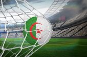 Football in algeria colours at back of net against large football stadium with lights