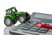 a tractor and a red pen is on a calculator. cost of gasoline, wear and insurance. costs and subsidies in agriculture