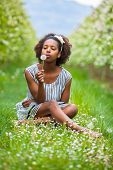 Outdoor Portrait Of A Young Beautiful African American Woman Blowing A Dandelion Flower - Black Peop