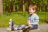 Smiling boy in rollers sits on walkway at park