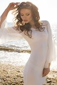 beautiful girl with dark hair in white dress posing on beach