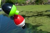 stock photo of fishing bobber  - two fishing bobbers on the line over water