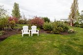 picture of manicured lawn  - Two white lawn chairs sit next to each other in a landscaped yard with manicured grass and a background of spring bushes and trees - JPG