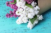 Beautiful bouquet of lilac flowers on color wooden background