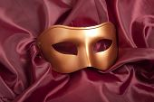 Golden carnival mask on red satin background