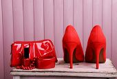 Red women shoes and beautician on wooden background