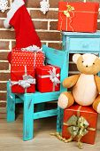 Christmas presents on chair and bookcase on brown brick wall background
