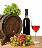 Wine in goblet and in bottle, grapes and barrel on wooden table on white background